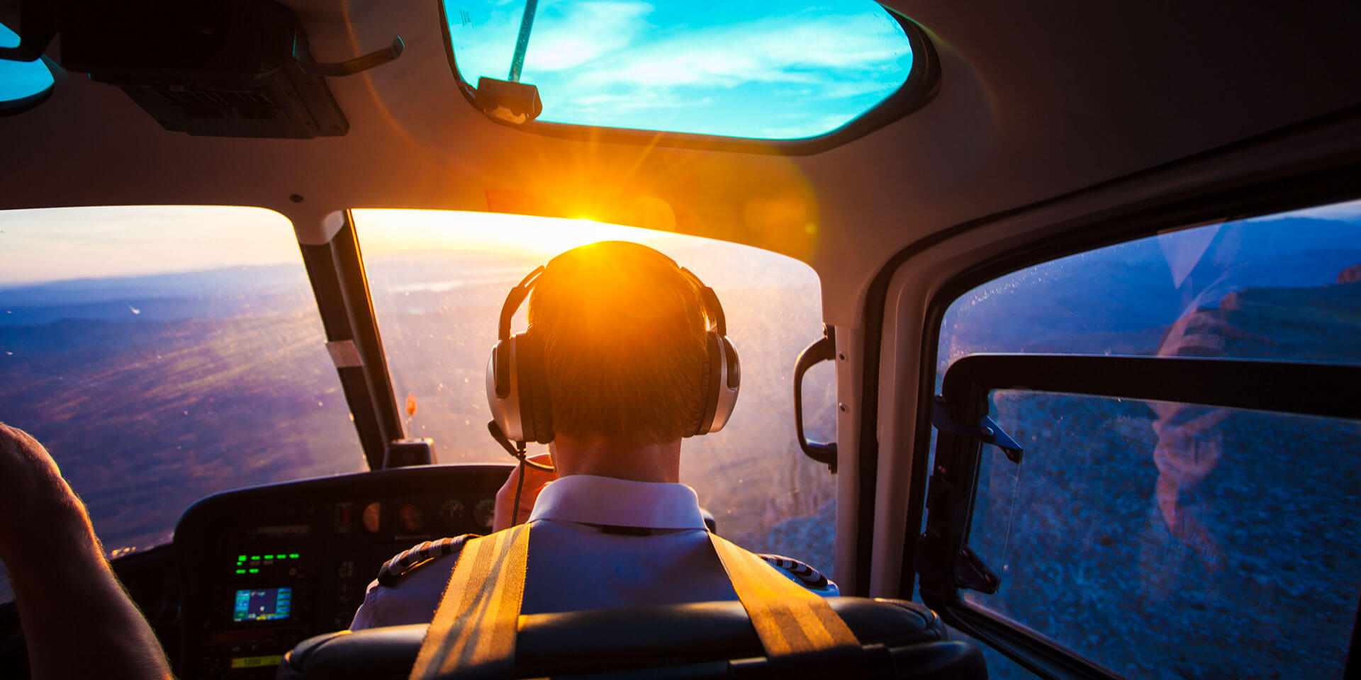 pilot flying a plane looking at the view with a sunset